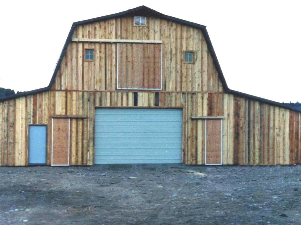 Gambrel roofed barn with custom wooden siding.