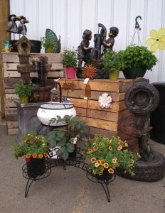 Greenhouse display that showcases planter stands holding flowers and yard fountains.