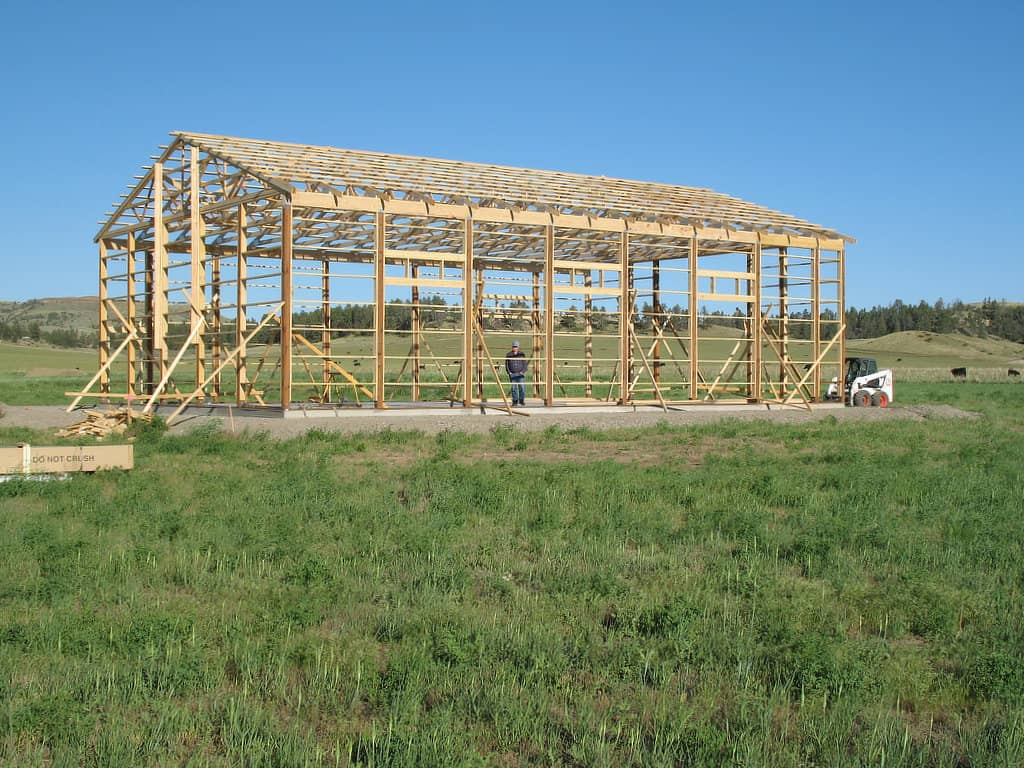 Completed wooden pole barn frame that includes posts, turned girts, and roof trusses.