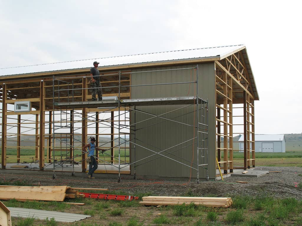 Scaffolding set up on one side of a wooden pole barn frame with steel siding starting to be installed.