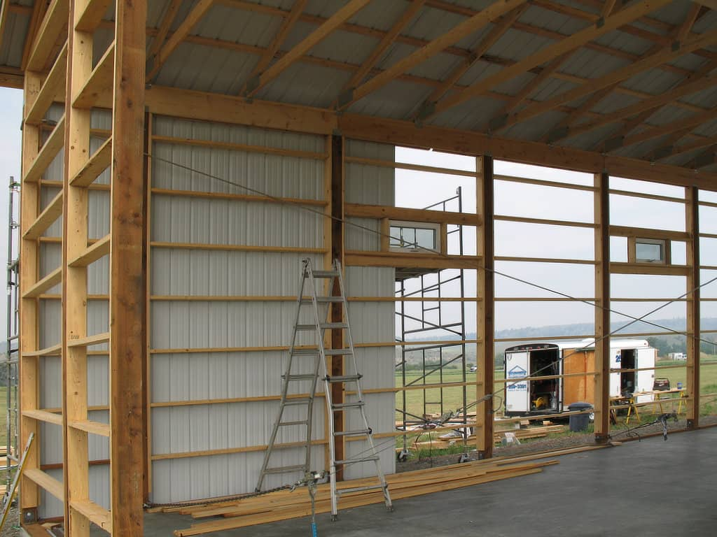 Interior view of a pole barn as the steel siding is being installed on the wooden frame.