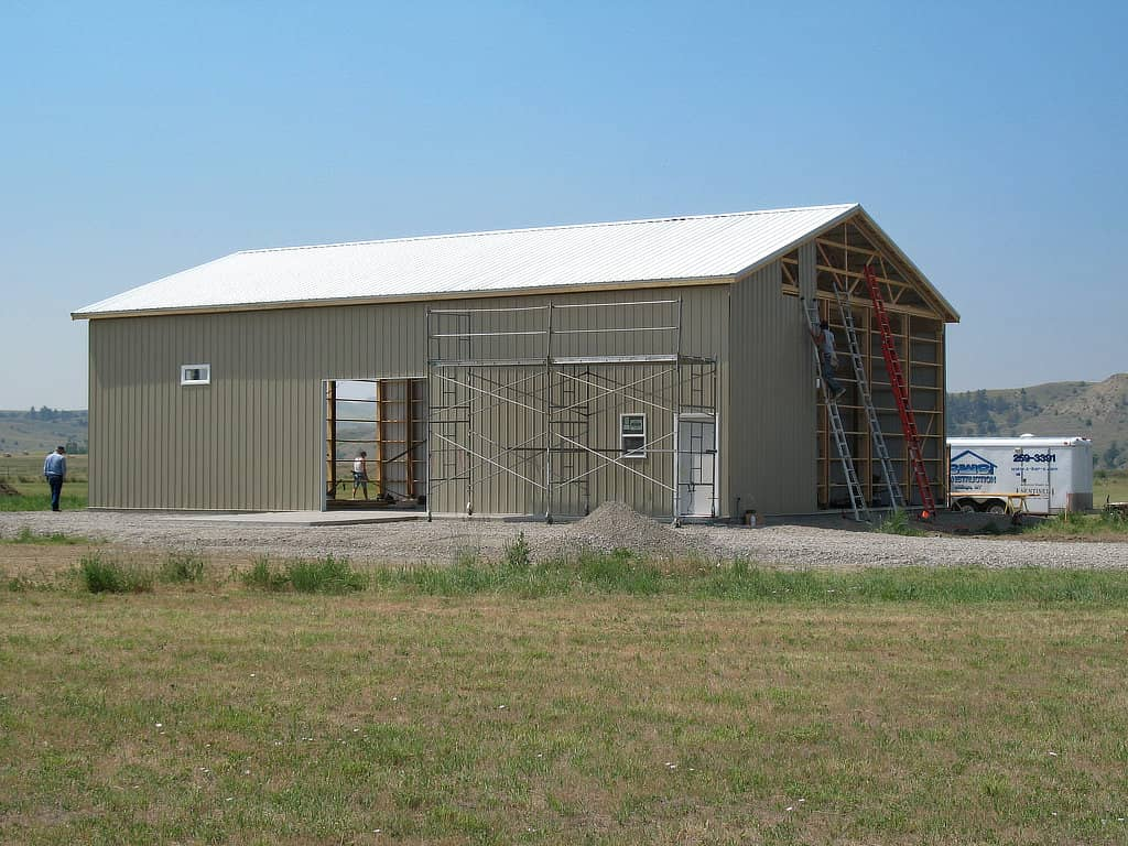 Man on a ladder installing a sheet of steel siding on the gable end of a pole barn.