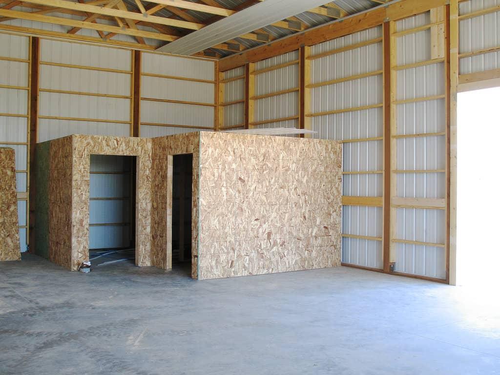 Future bathrooms under construction inside a pole barn.