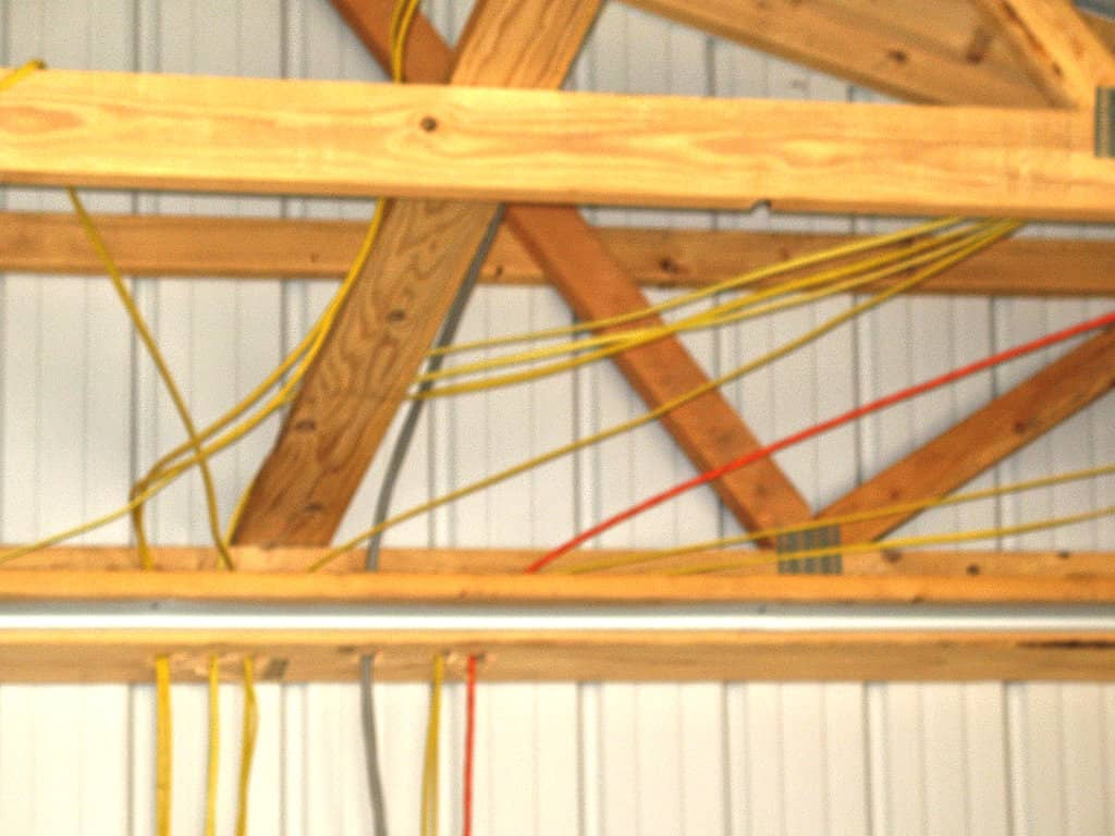 Electrical wiring coming down from the exposed roof trusses and wall frame of a pole barn that is under construction.
