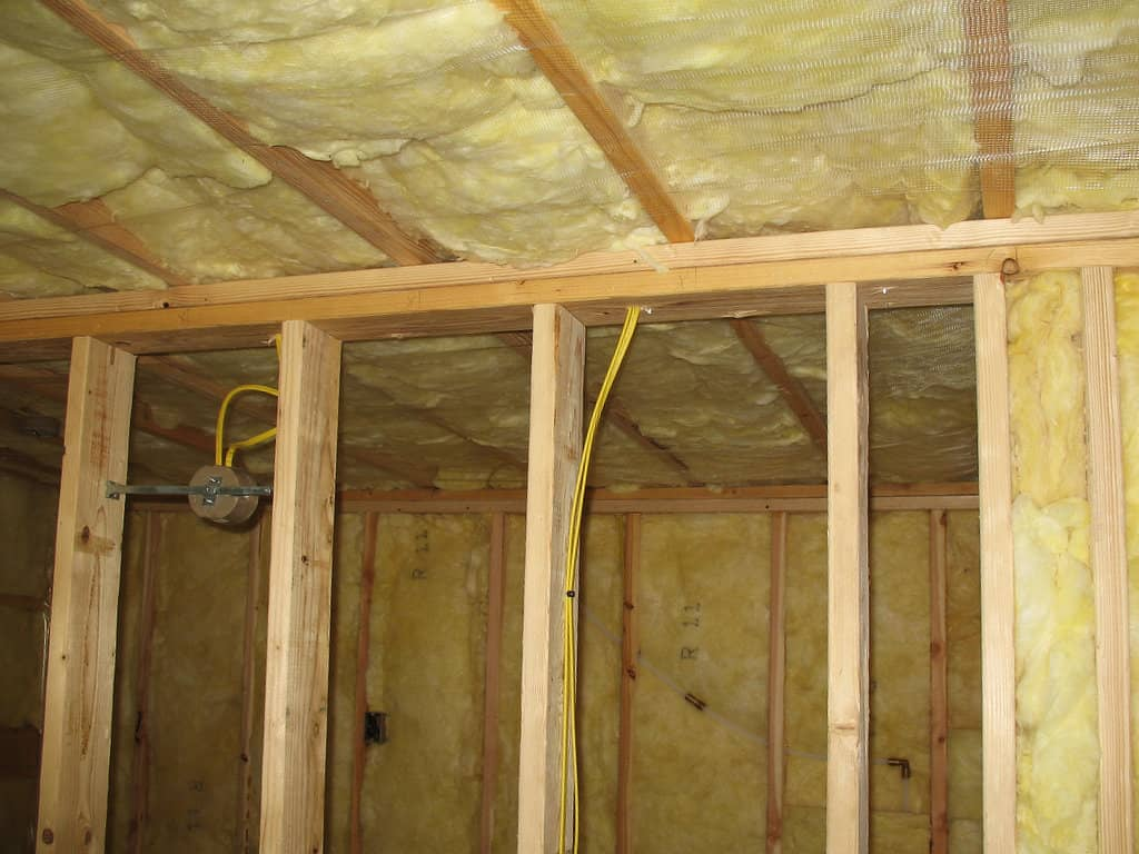 looking through the frame of an interior wall to the installed fiberglass insulation in the exterior walls and rafters.