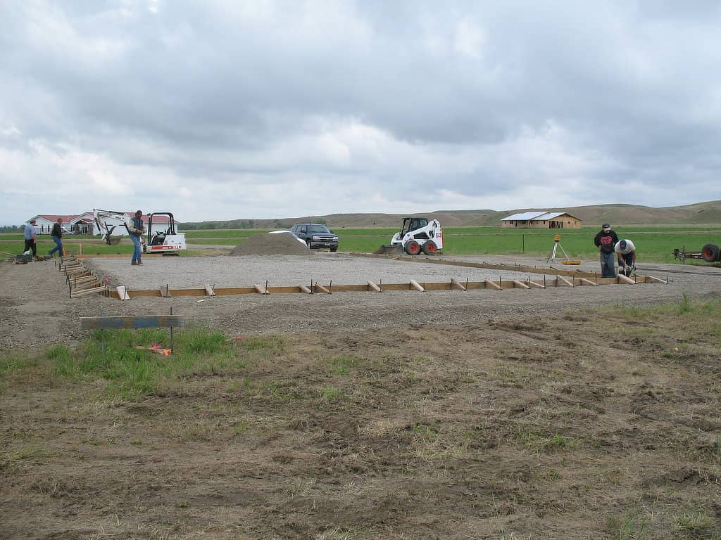 Workers prepping the sub-base and form for a concrete slab.