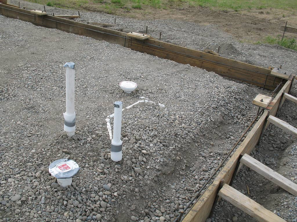 Exposed plumbing within the concrete form that will be a slab for a pole barn.