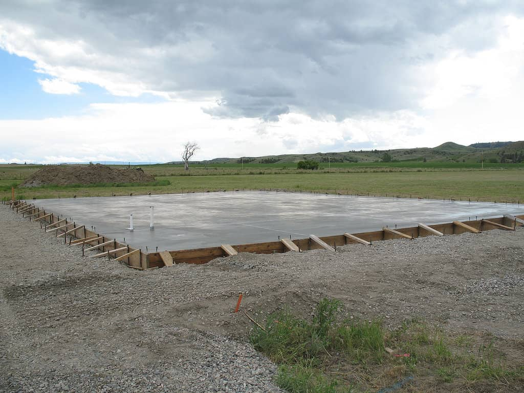 Concrete slab for a pole barn curing in its form.