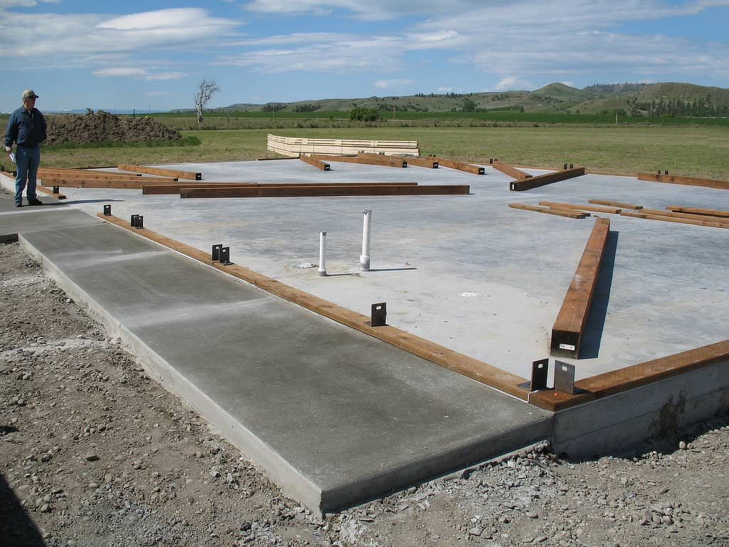 Base plates on a concrete slab with anchors awaiting the post for a pole barn.
