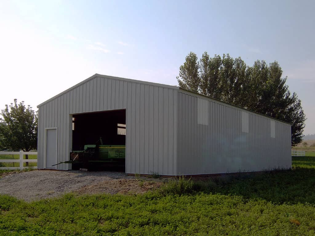 Pole building with light panels along the sides and farm equipment shown in the oven overhead door.