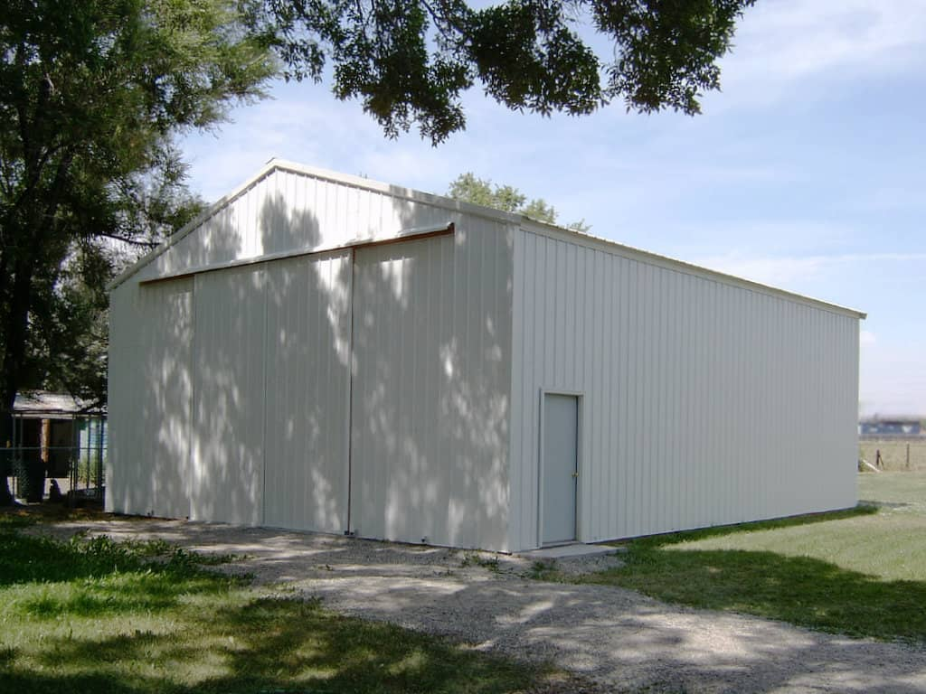 White steel-clad pole building with sliding barn doors on a gable end.