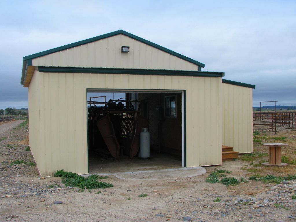 Angled view of a small pole barn with open overhead doors on each end and housing agricultural equipment.