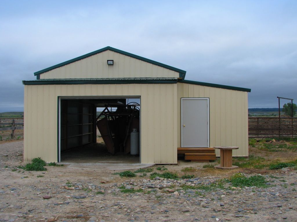 Front view of a small pole barn with open overhead doors on each end and housing agricultural equipment.