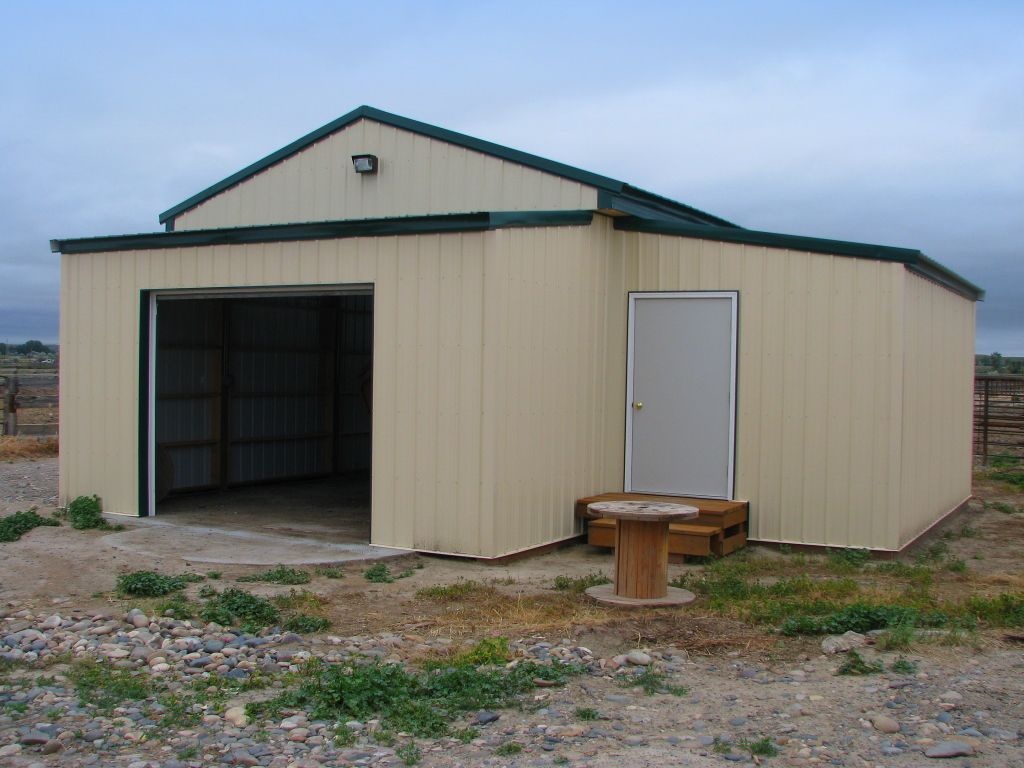 Small pole barn with two side additions, all covered in cream-colored steel siding.