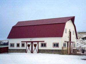 Gambrel pole barn with red steel roof. Sliding barn doors and rock wainscot are on the side.