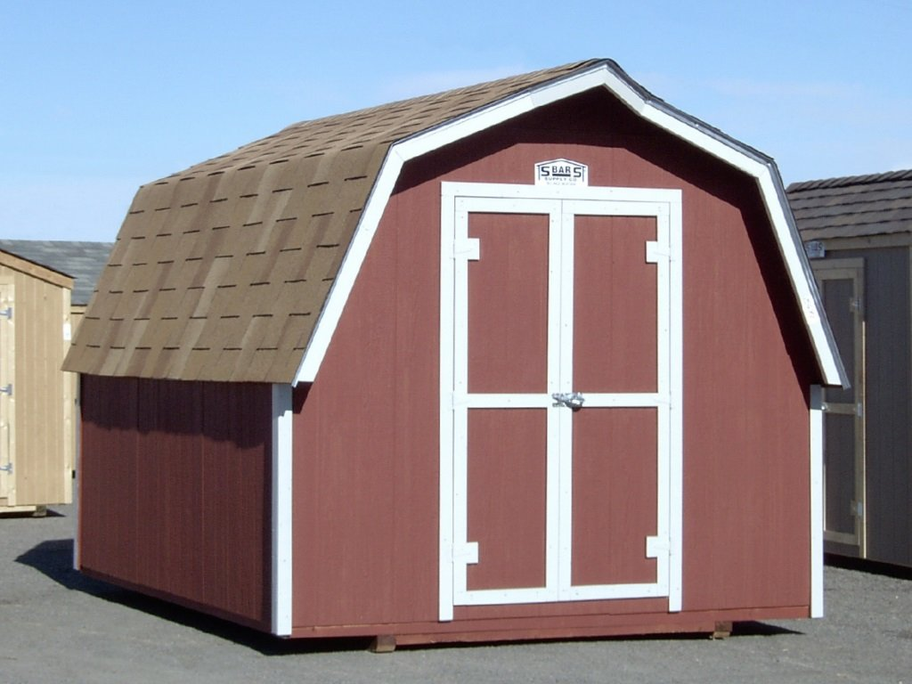 A barn-style shed with it's eaved, gambrel roof covered in shingles and having red-painted wooden siding with white trim.