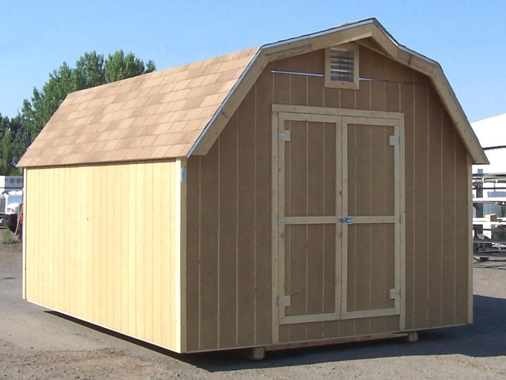 A barn-style shed with it's eaved, gambrel roof covered in shingles and having wooden siding.