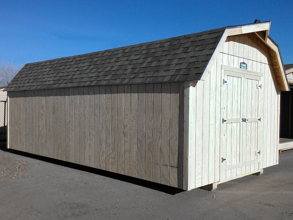 A barn-style shed with it's eaved, gambrel roof and wooden T1-11 siding.
