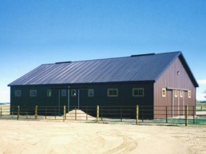 Gable roofed pole barn with black metal roofing and trim. The walls are sided with brown metal and have sliding barn doors.