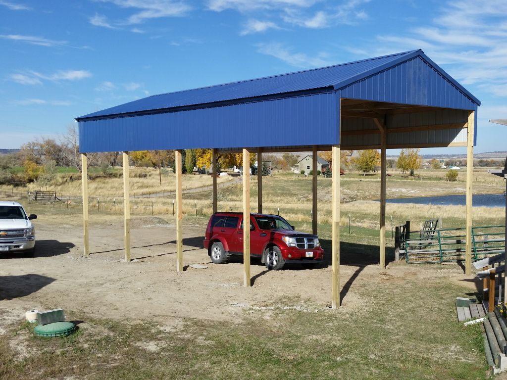 A blue metal topped carport supported with wooden posts and having a red SUV parked underneath.