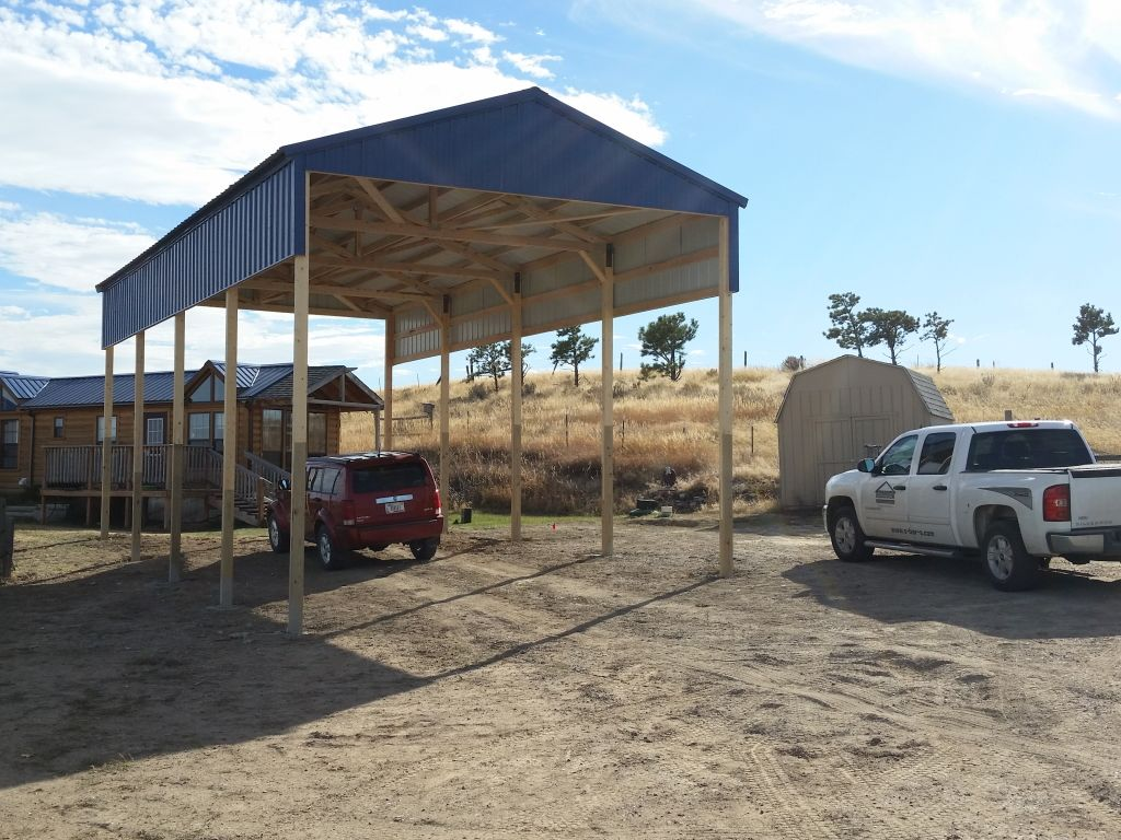 A blue steel topped carport built with post frame construction.
