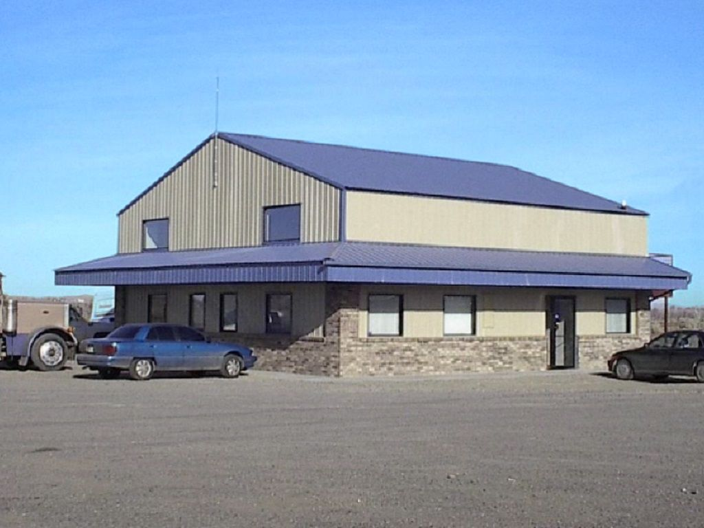 Commercial retail building sided in tan steel and having a blue steel roof and awning over the entrance doors.