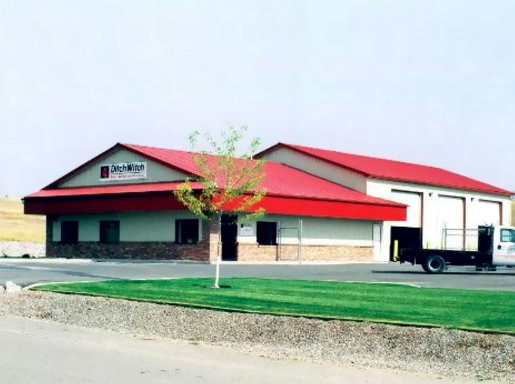 Red steel roof on a commercial shop and office building. A red steel awning covers the office portion.