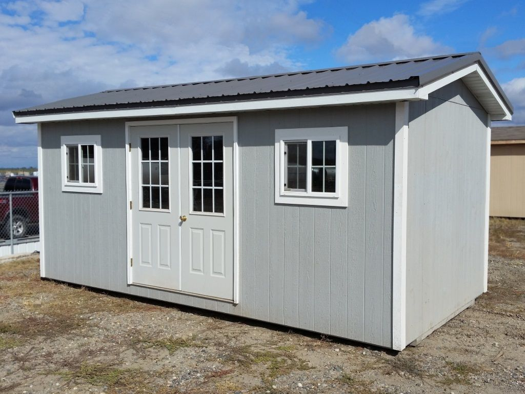 Custom shed built to be a backyard office with french doors and two windows.