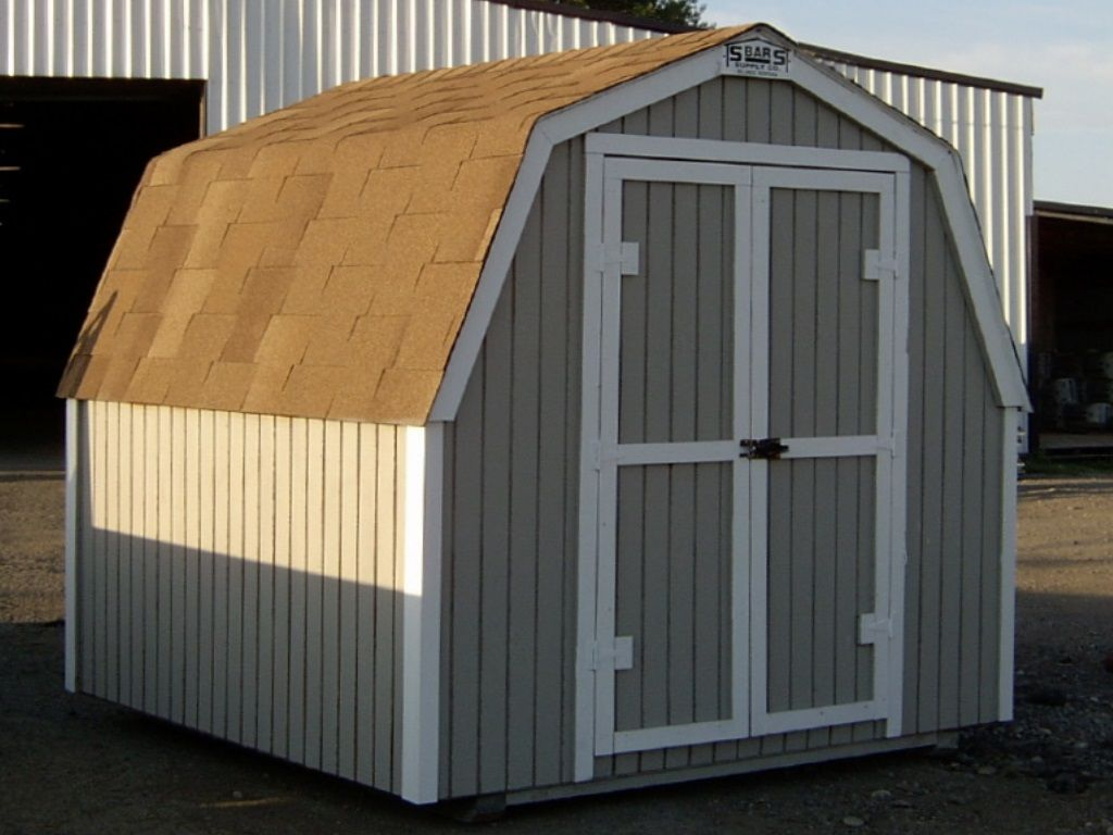A barn-style shed with a gambrel roof, no overhang and covered in tan shingles. It has hardboard siding and white trim.