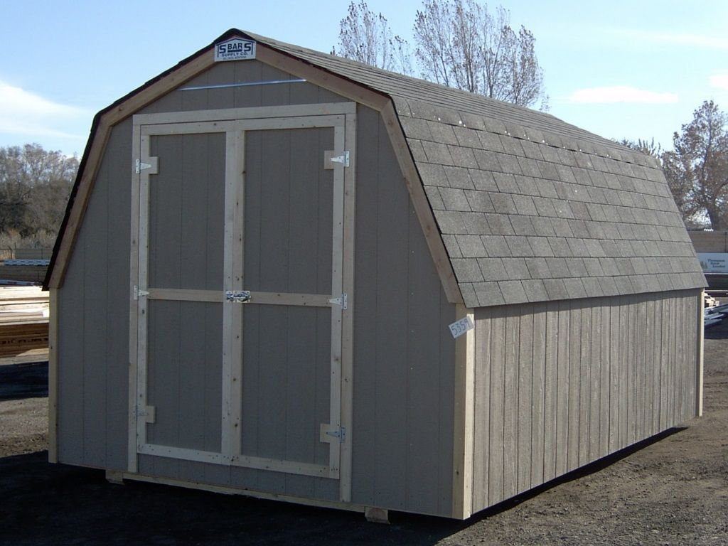 A barn-style shed with a gambrel having no overhang. The roof is covered in gray shingles and it has hardboard siding.