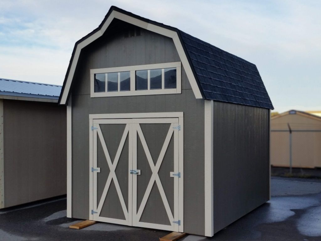 Custom shed with shingle covered gambrel roof and a horizontal window above the shed door. The shed is gray with white trim.
