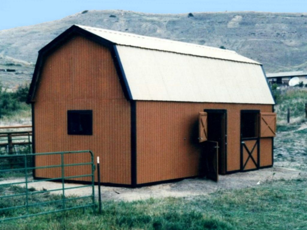 Gambrel pole barn with wood siding and two stall doors.