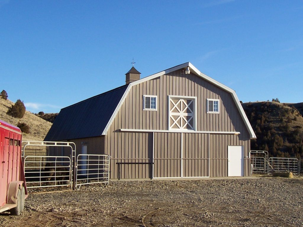Front of a gambrel-roofed pole barn with a cupola. A sliding barn door are at the end along with a walk door.