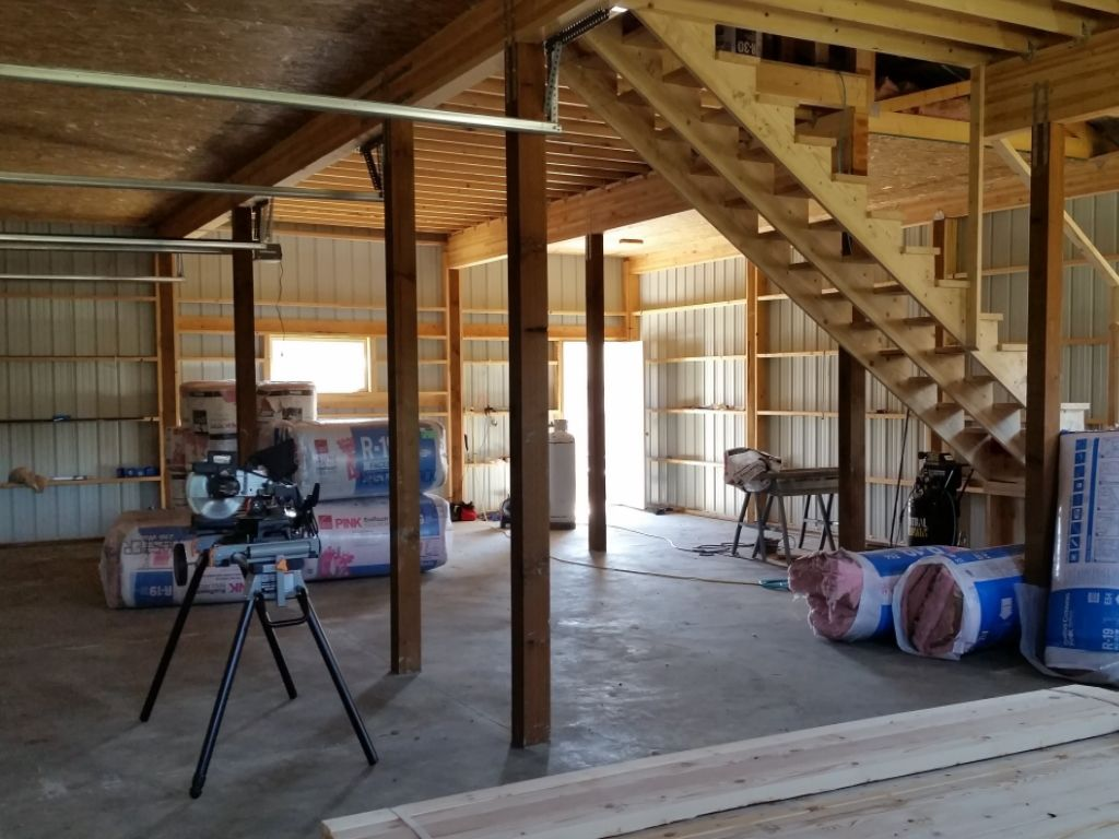 Interior of pole building garage with turned-girt framing and insulation batts waiting to be installed.