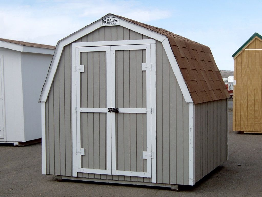 A barn-style shed with a gambrel roof, no overhang and covered in tan shingles. It has gray-painted siding and white trim.
