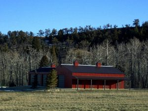 Red-sided pole barn with a brown steel roof sitting among the trees.