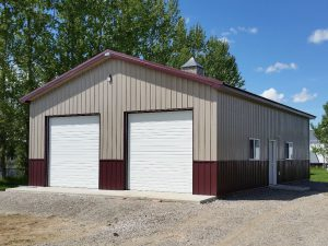 Two car garage and shop with overhead doors on the gable end. Building has burgandy wainscot and a cupola.