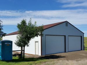Two car garage and shop with overhead doors on the gable end. Building has white steel siding and a brown steel roof.