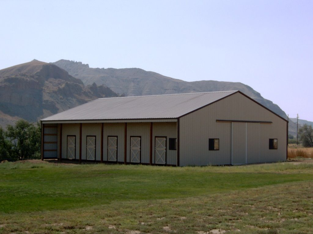 Gable roofed barn with a lean-to on one side to cover stall doors and a sliding barn door at the end.
