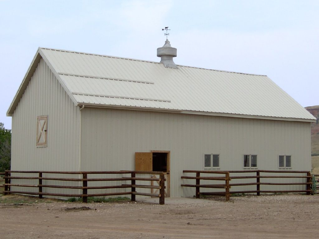 Gable-roofed pole barn with snow-stop on the roof over the stall door.