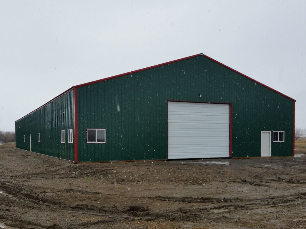 Large pole building shop with green metal siding and red metal trim and roofing.
