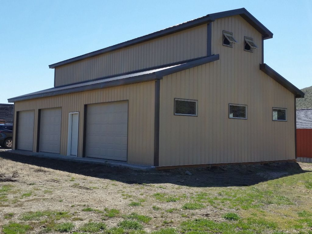 Three bay garage with monitor style roof, tan steel siding and dark brown steel roof.