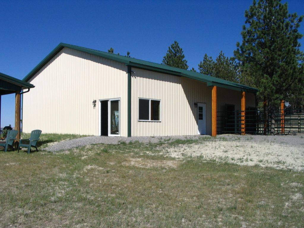 Cream steel siding and a forest green steel roof are on a pole barn built by S-Bar-S.