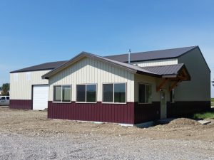Light tan steel siding enhanced with a burgandy wainscot on a post-frame shop and office built by S-Bar-S.
