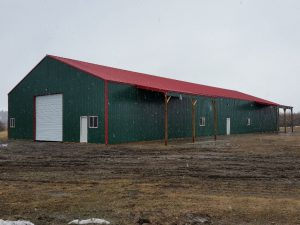 Pole barn shop with red metal roof, sided in green steel, and having two lean-tos on one side.