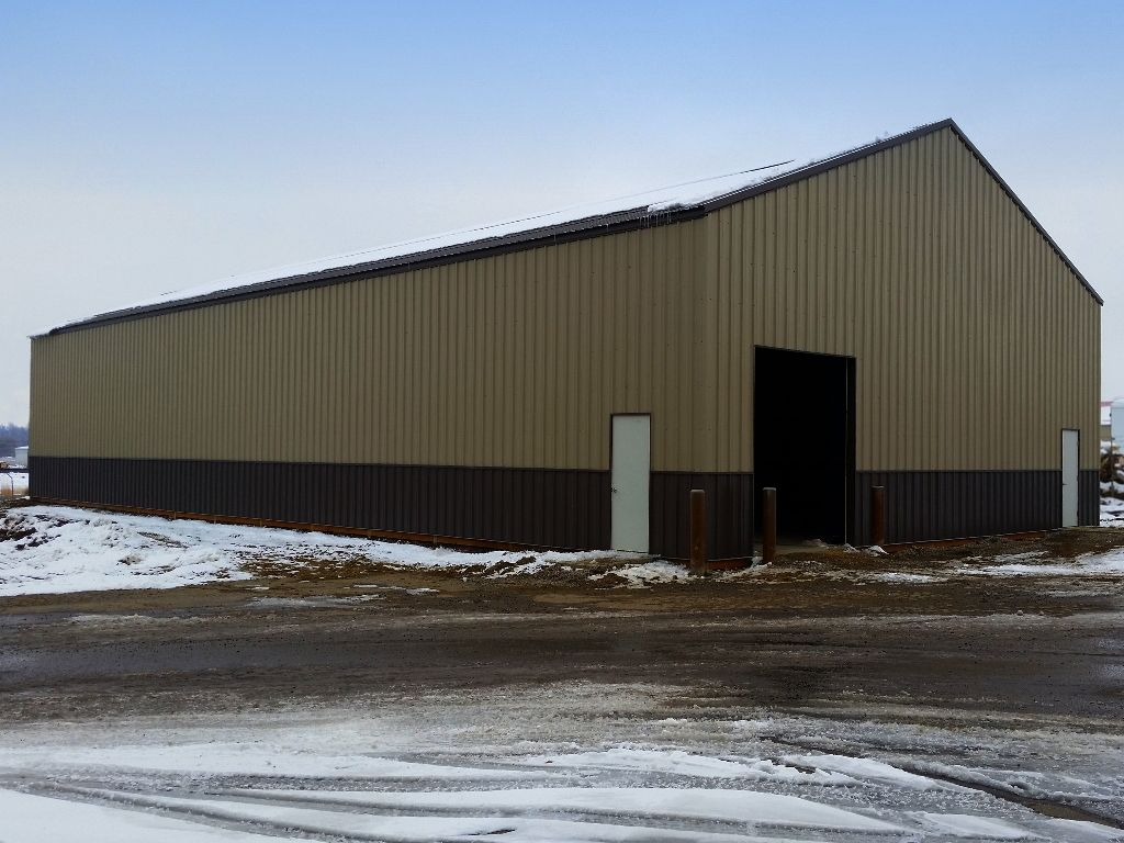 Post-frame steel building with an overhead door and two walk doors, A brown steel wainscot surrounds the building siding.
