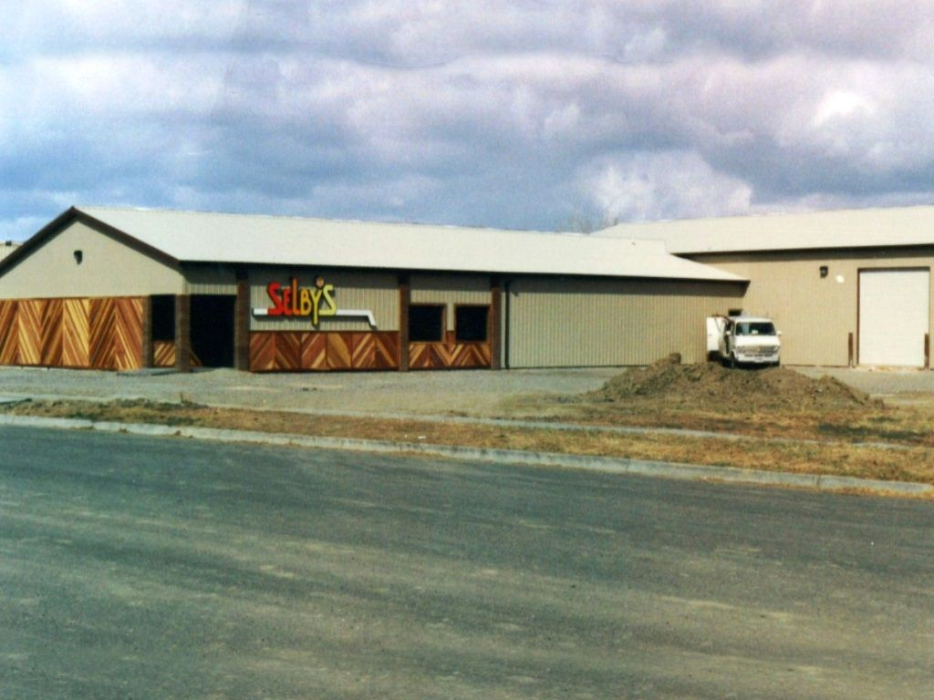 Retail and shop building that has steel siding with a custom wood wainscot in a herringbone pattern.