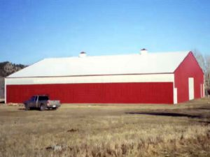 Gable roofed pole barn with red steel siding. Fiberglass light panels line the upper wall.