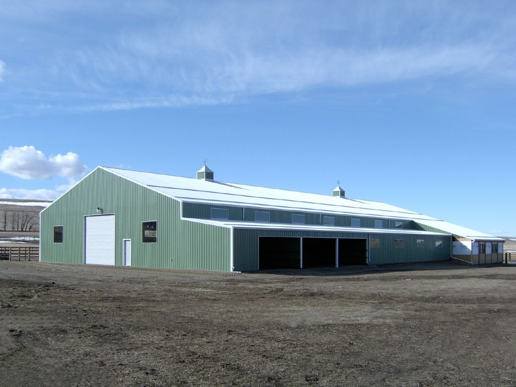 Light green steel siding covers a gable-roofed riding arena adorned with two cupolas. A covered lean-to lines one side.