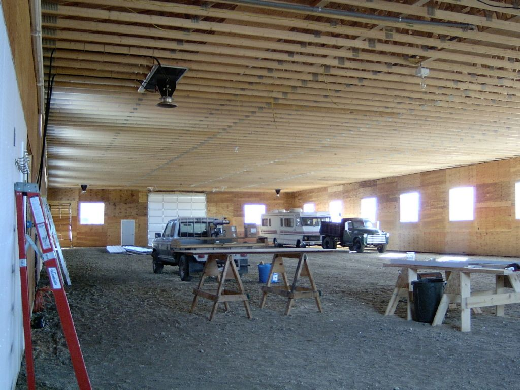 Interior of a riding arena that is still under construction. Roof trusses are visible.